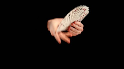 Magician make performance with playing cards on black background