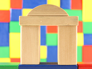 helle Bausteine vor bunter Wand aus Bauklötzen
