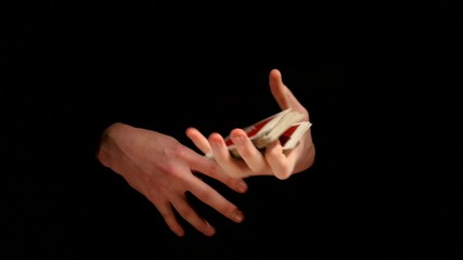 Magician shows his trick with playing cards on black background
