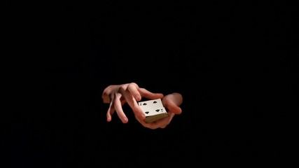 Magician making trick with playing cards on black background