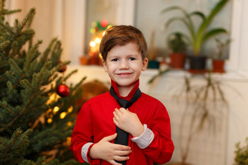Little boy holding tie at Christmas