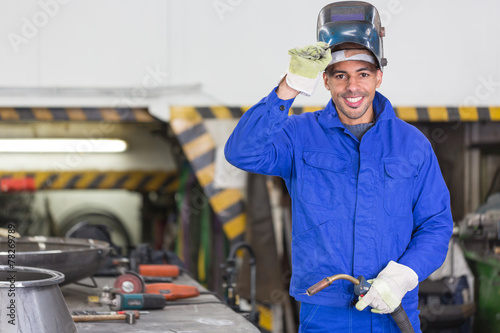 Professional welder posing with wellding machine - 78269789
