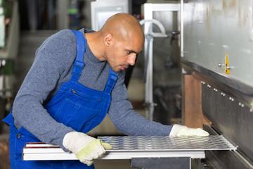 Worker operating machine for bending sheet metal