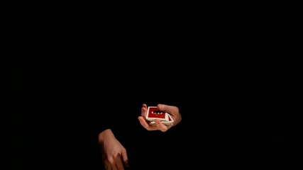 Wizard showing trick with playing card on black background