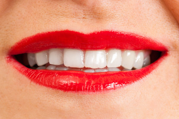 female open lips with applied red lipstick, white teeth