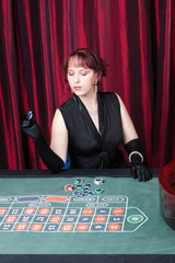 woman wearing black dress and gloves plays in a casino