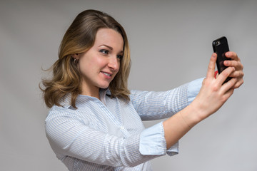 Business Woman holding a cell phone taking a picture