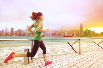 Urban runner woman jogging in Hong Kong at sunset