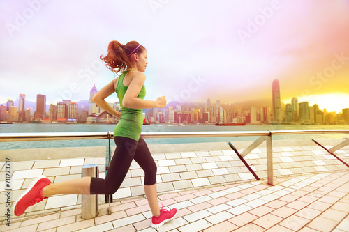 canvas print picture Urban runner woman jogging in Hong Kong at sunset