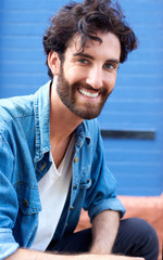 Cheerful young man with beard smiling
