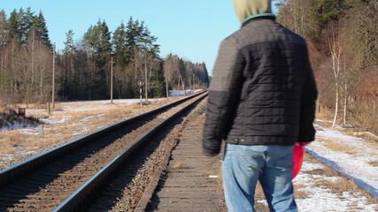 Man with red heart-shaped balloon near railway