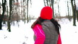 Woman running on the snow in the forest, steady, slow motion