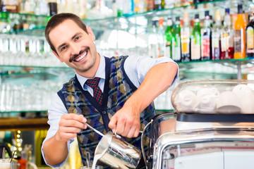 Barista in cafe or coffee bar preparing cappuccino