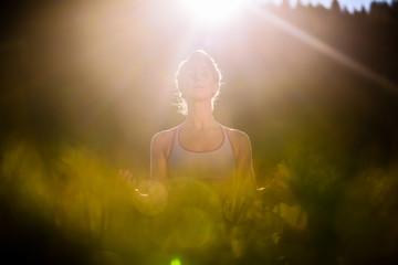 Frau bei Yoga im Sonnenuntergang