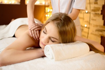 Young beautiful woman lying on a massage table