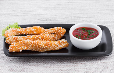 Fried fish fingers with sauce and sesame