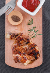 Juicy grilled fillet steak with tomatoes dip on an wooden board