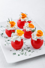 Many small tomatoes stuffed with cream cheese