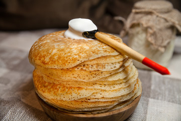 Блины на деревянной тарелке и ложка со сметаной