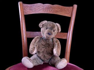 Antiker Teddy sitzt auf einem antiken Stuhl