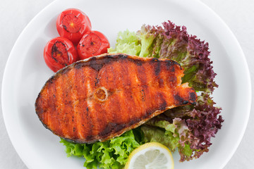 Grilled salmon, cherry tomatoes, lettuce and lemon