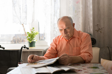 Old Bald Man Reading News Updates on Tabloid