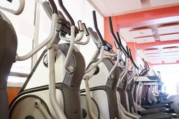 Elliptical cross trainer in a row in a gym