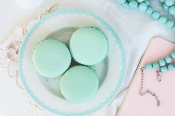 Mint macaroon and teal beads on light background