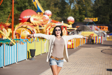 A young woman is happy and jumps. Amusement park rides.