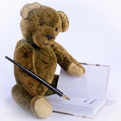 Antiker Teddy schreibt mit einem Füllfederhalter in ein Buch
