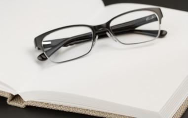 Black glasses on book