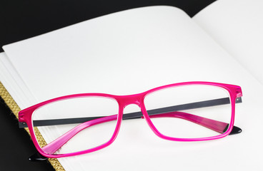 Folded pink glasses on book