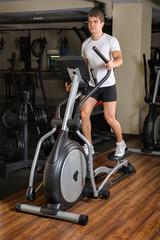 Man's Workout On Elliptical Machine
