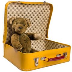 Antiker Teddy Bär in einem gelben Koffer will verreisen