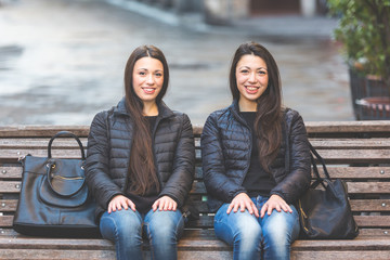 Two Female Twins Sitting on a Bench in the City
