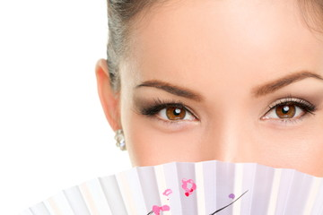 Asian beauty eyes - makeup woman looking with fan