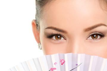 Asian beauty eyes - makeup woman looking with fan