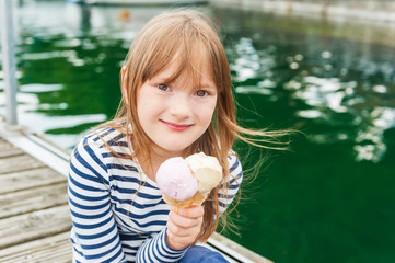 Outdoor portrait of a cute little girl, eating ice cream