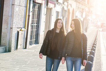 Female Twins Walking on Sidewalk in the City