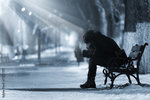 Leinwanddruck Bild Depressed woman on a bench
