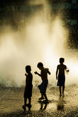 Silhouette of three kids playing in a fountain