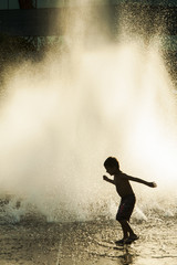 Boy playing in front of a fountain