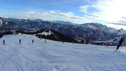People skiing down on ski slope, Austria, Alps, pov
