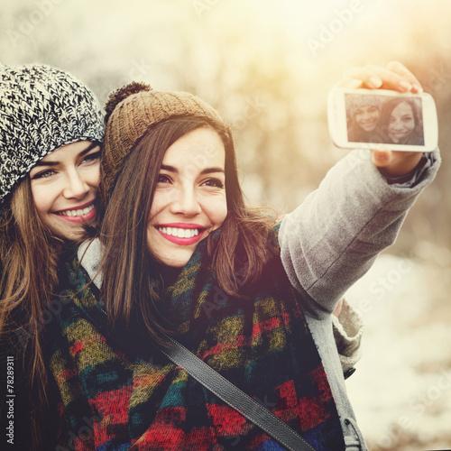 Two teenage girls taking a selfie outdoors in winter - 78289311