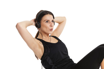 Beautiful lady with headphones train her abs. Isolated on white