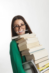 student female holds many books with a pen in mouth