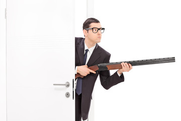 Businessman holding rifle and entering a room