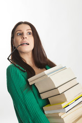 student female with glasses in her mouth holds many books.