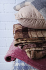 Warm plaids and pillow on white brick wall background