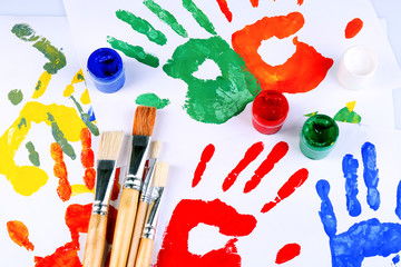 Hand prints of paint, paints and brushes on white background